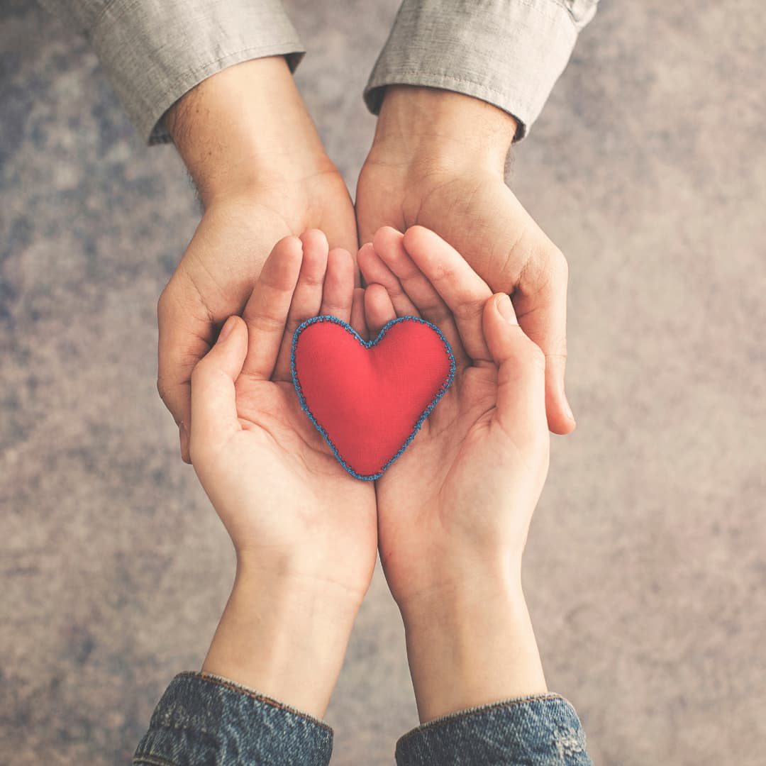 Two people holding a heart